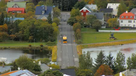 hallgrimskirkja : bright yellow bus moves over bridge of lake Tjornin in Reykjavik in autumn time, top view