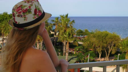 exotikou : young blonde woman wearing a vivid hat, looking at sea and palm garden, dreaming Dostupné videozáznamy