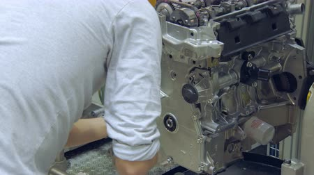 wrench : worker is putting bolts into car engine, modern car production, workshop Stock Footage