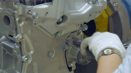 затянуть : close up of tightening bolts in car engine, by worker, hands with gloves, special tool