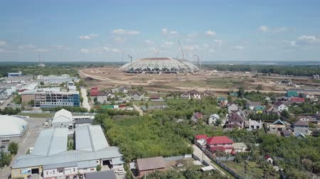 ассоциация : construction of stadium in Samara city, aerial shot in sunny day, summertime, small houses are near
