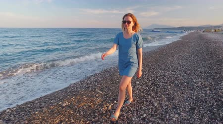 marítimo : young slim blonde is wearing blue dress and sunglasses is strolling on pebble seashore Vídeos