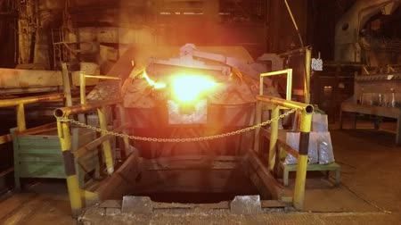 elektrownia : camera is moving forward to blast furnace, in foundry in metallurgical plant, dark workshop and red-hot aluminium