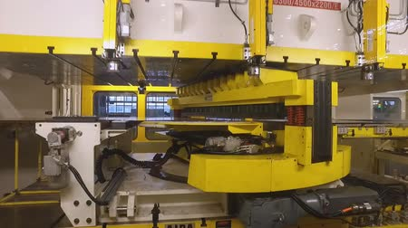 çinko : camera moves to four square windows to press cutting machine, preparation for making car body