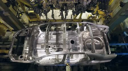 brake : car bodies are moving on conveyor, robotic production in automobile factory, welding