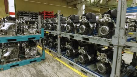 седан : prepared car engines are standing in shelfs in workshop of modern automobile factory, moving shot