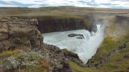 gullfoss : Gullfoss waterfall in cloudy weather, dramatic clouds, many tourists are visiting, in summer day Stock Footage