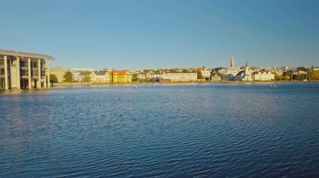 экологически : panorama of lake Tjornin in centre of Reykjavik in Iceland with parliament building, sunny Стоковые видеозаписи