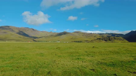 snow caps : panorama of picturesque green fields and static clouds in Iceland, near volcano Eyjafjallajokull Stock Footage