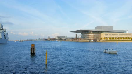 copenhagen : small boat is floating on Oresund strait near Copenhagen Opera House in sunny autumn day