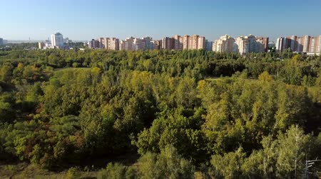 volga region : drone is flying over green summer forest near modern city in sunny weather, moving to houses Stock Footage