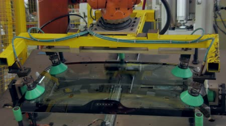 emme : robot is gripping a back car windows and lifting up in a car factory