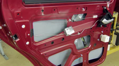 mechanically : door of automobile, painted red color, in a car factory, preparing for assembly and mounting
