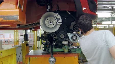 repairer : installing an engine in a car on an automobile plant, worker is using auto hydraulic lift