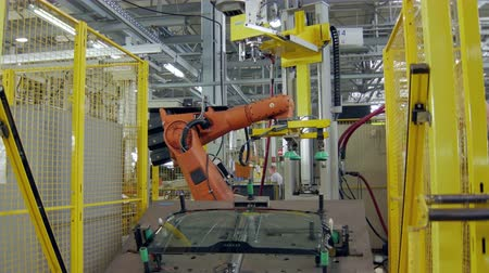 automatický : workerman is installing a car windows on a platform of robotic machinery for hermetization