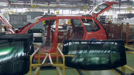 часть тела : car body is moving slowly on a conveyor in a factory shop, windows for automobiles are lying