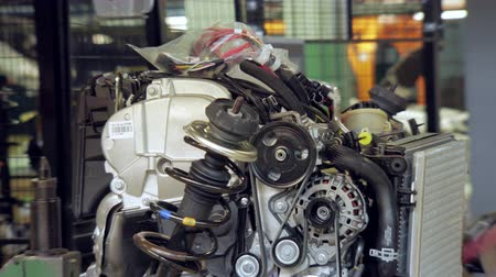 csavarkulcs : transfering car engine to automobile for installation, worker is controlling
