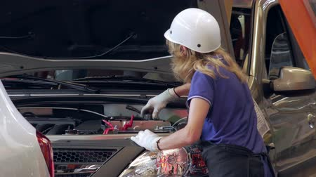 vehicle part : worker woman is tightening caps of capacities for technical liquids inside a car on a car factory Stock Footage