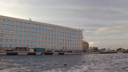 copenhagen : large modern industrial building are on a shore, view from boat, in evening time