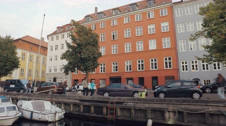 copenhagen : Copenhagen, Denmark - OCT, 2016:people are walking on a quay, traditional multicolor living houses and sailboats, view from pleasure boat