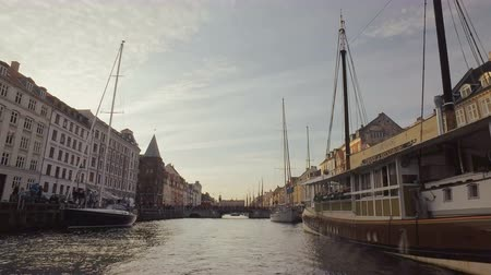copenhagen : Copenhagen, Denmark - OCT, 2016: moored old traditional sailboats in Nyhavn, New Harbour in evening, view from centre of a channel from a ship Stock Footage