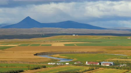 nordic countries : rural suburban landscape in Iceland in sunny autumn day, calm river, mountains, agricultural fields Stock Footage