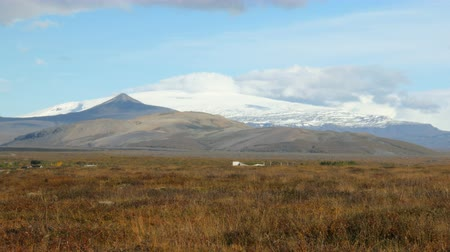 glaciation : icelandic old glacier in sunny weather, clouds are on the top, view from dry fields in autumn time Stock Footage
