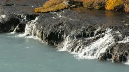 hraunfossar : clear water is flowing from rocks into rapid mountain river light blue colored Stock Footage