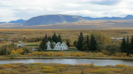 local : Oxara river in icelandic national park Thingvellir in fall day, buildings are on shore