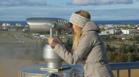 periscope : young tourist girl is looking in a stationary telescope on Reykjavik in sunny day