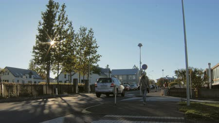 outskirts : blonde woman is crossing a pedestrian passages in suburban area in sunny autumn day