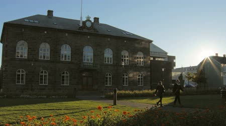 kurmak : Reykjavik, Iceland - SEP, 2016: old historical building of parliament in downtown with walking people in sunny fall day Stok Video