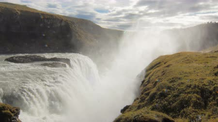 gullfoss : amazing large waterfall in sunny day in Iceland, splashes are flying up, cloudy sky in background Stock Footage