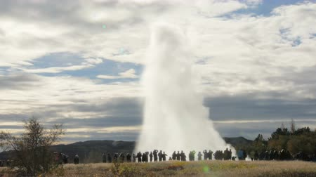 strokkur : eruption of Strokkur geyser, view from distance from backs of tourists, in sunny daytime in a fall Stock Footage