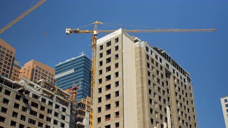 urbanística : panorama from clear blue sky to buildings under construction with cranes in summer day Vídeos