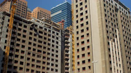 urbanística : vertical panorama of two high buildings under construction in center of modern city in sunny day