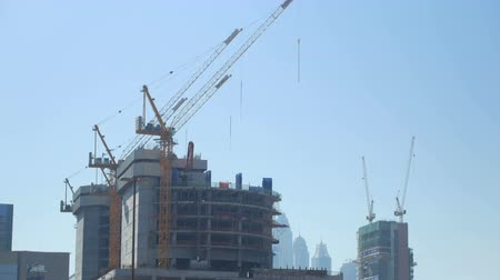 urbanística : tilt up panorama of huge construction cranes are in unfinished building in big modern city