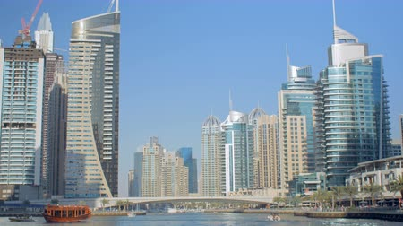 pleasure boats : amazing panorama of modern skyscrapers on a coasts of fake canal against clear blue sky