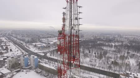 vysílač : drone is flying over city panorama and showing tall tv tower in winter day
