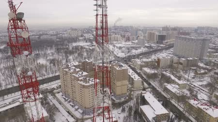 microonda : camera is lifting along a modern telecom tower, aerial view on buildings and roads of city