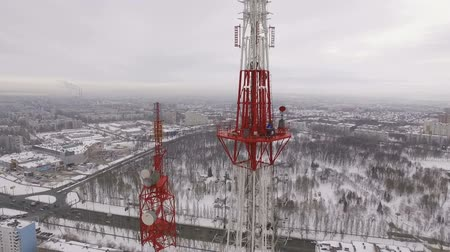 truss : workers are climbing on a telecom tower, other men are performing repair on a site, aerial view Stock Footage