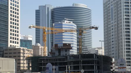 real : unfinished building in a modern district of city in summer day, workers and crane