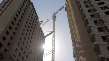 urbanística : two high houses under construction in sunny day, crane is standing against sun