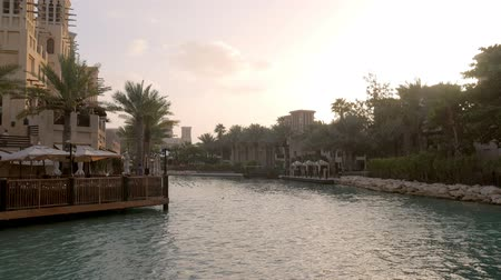 восточный базар : landscape with canal, tropical palms and traditional arabic buildings with cafe in evening Стоковые видеозаписи