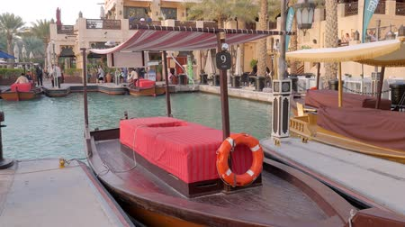 pleasure boats : boat stylised like traditional arabic small vessel with fabric roof for riding tourists in Dubai Stock Footage