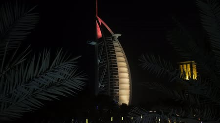 seasons changing : DUBAI, U.A.E. - JAN, 2018: building of Burj Al Arab hotel in night against black sky, palm leaves