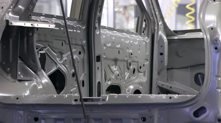 unfinished : close-up of car body, moving in conveyor in automobile plant Stock Footage