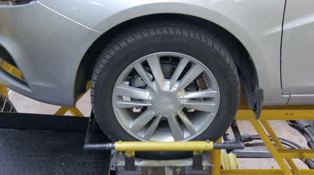 bracket : equipment in laboratory is shaking a wheel of new automobile in car plant