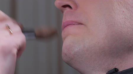 bochecha : close-up of bottom face of adult man, makeup artist is touching his skin by brush Stock Footage