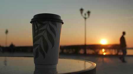passerby : one coffee cup is standing on a table of a street cafe in background of embankment, sunset sky